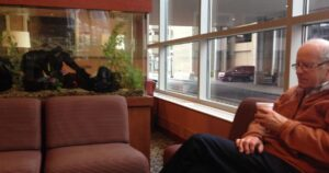 My dad sitting near a fish tank in a hospital waiting room