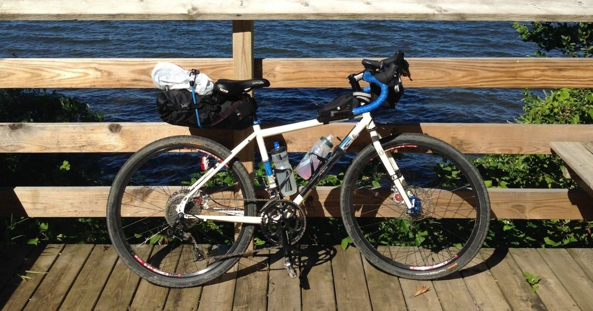 Salsa Vaya bicycle with packs alongside fence by a lake