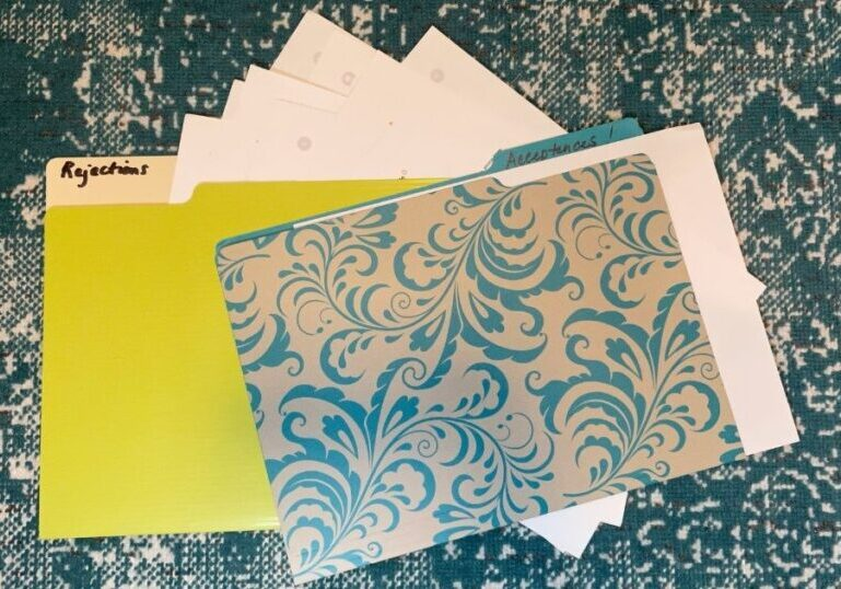 two file folders, a green one and a turquoise and gray floral one labeled Rejections and Acceptances! Several sheets of paper visible sticking out from folders.