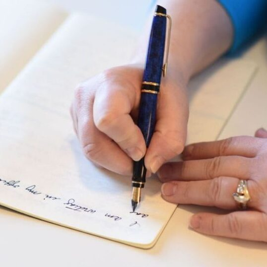 a hand holding a blue fountain pen, another hand on the page of a journal. Pen is writing words in cursive in the journal